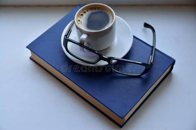 Filiżanka kawy na czytelniczej książce z szkłami obraz stock
