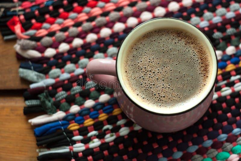 Filiżanka kawy na drewnianym tle z tkanina wyplatającym gałganianym dywanikiem Odbitkowa przestrze?, odg?rny widok fotografia royalty free