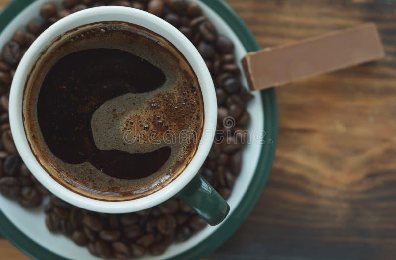 Filiżanka kawy na spodeczku z piec kawowymi fasolami i kawałkiem czekolada fotografia royalty free