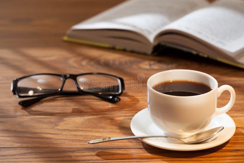 Filiżanka kawy, otwiera książkę i szkła na biurku obrazy royalty free