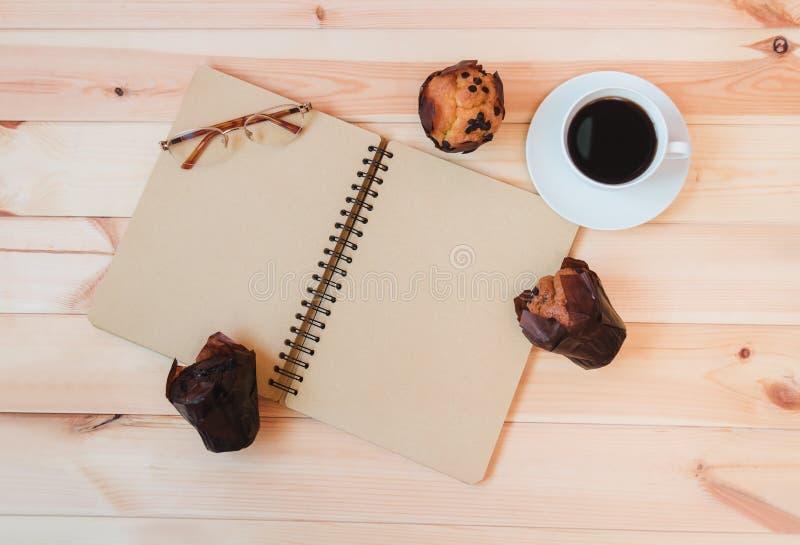 Filiżanka kawy, pusty notatnik i muffins, fotografia stock