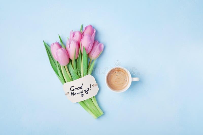Filiżanka kawy, różowi tulipanów kwiaty i nutowy dzień dobry na błękitnym stołowym odgórnym widoku, Piękny śniadanie na matek lub fotografia stock