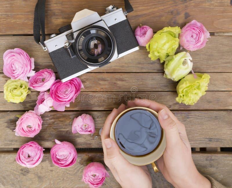 Filiżanka kawy trzymająca w dwa rękach na drewno stole z klasyczną fotografii kamerą wokoło z kolorowymi kwiatami zdjęcia stock