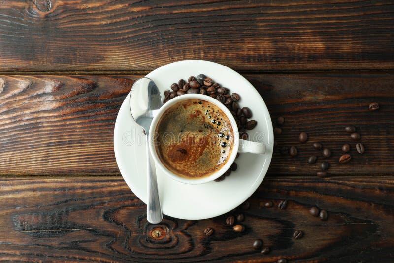 Filiżanka kawy z łyżkowymi i kawowymi fasolami na drewnianym tle, przestrzeń dla teksta zdjęcia stock