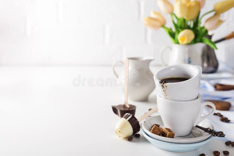 Filiżanka kawy z żółtymi tulipanami odizolowywającymi na białym tle zdjęcie stock
