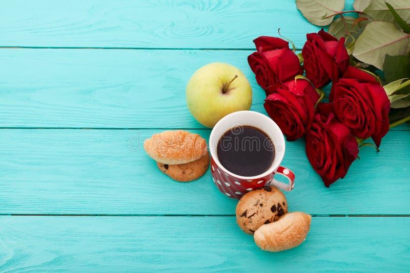 Filiżanka kawy z croissants, ciastka, jabłko, czerwone róże na błękitnym drewnianym tle kosmos kopii Egzamin próbny Up Odgórny wi obraz royalty free