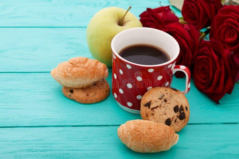 Filiżanka kawy z croissants, ciastka, jabłko, czerwone róże na błękitnym drewnianym tle kosmos kopii Egzamin próbny Up Odgórny wi obrazy stock