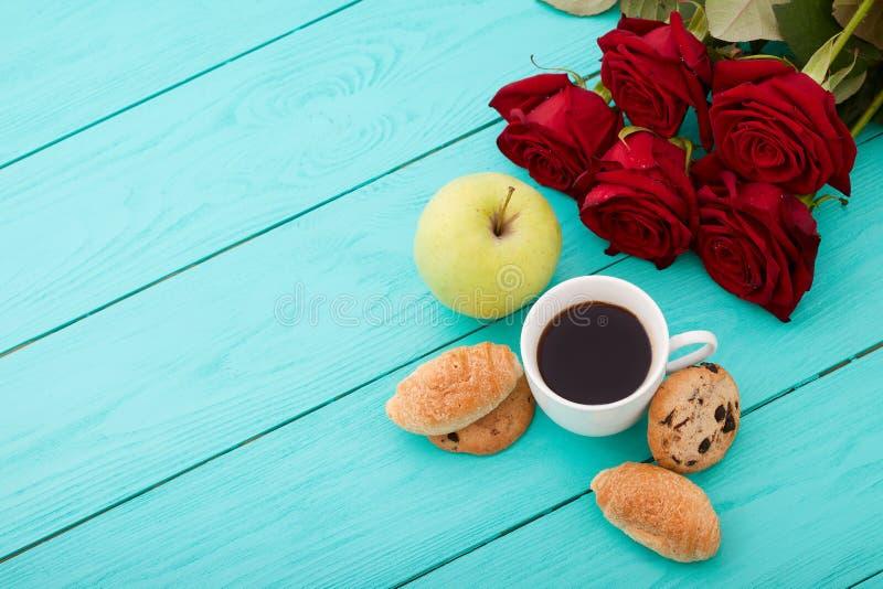 Filiżanka kawy z croissants, ciastka, jabłko, czerwone róże na błękitnym drewnianym tle kosmos kopii Egzamin próbny Up Odgórny wi zdjęcia royalty free