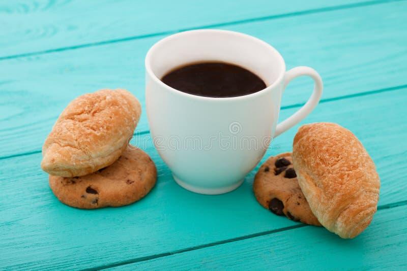 Filiżanka kawy z croissants na błękitnym drewnianym stole Selekcyjna ostrość fotografia royalty free