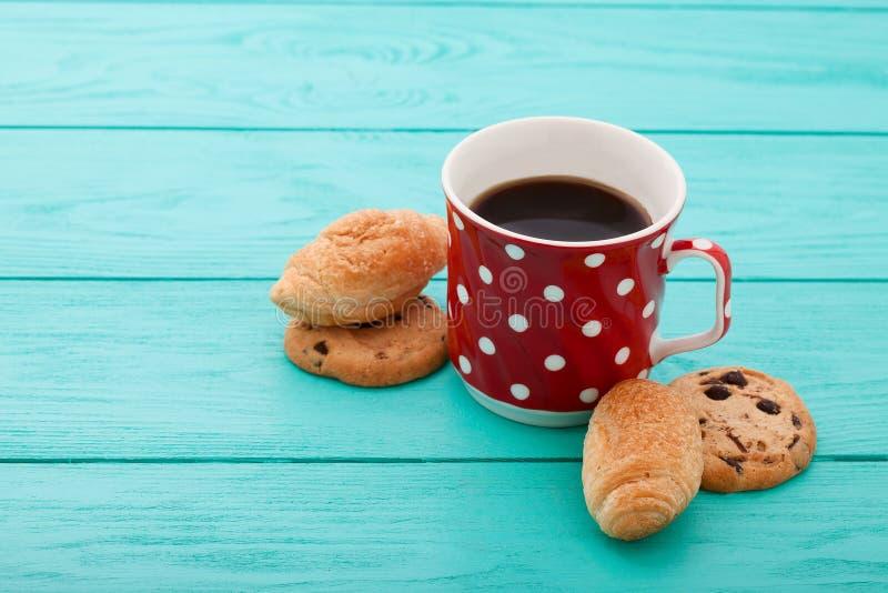 Filiżanka kawy z croissants na błękitnym drewnianym stole Selekcyjna ostrość zdjęcie royalty free