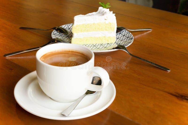 Filiżanka kawy z kawałkiem tort na drewnianym stole w kawiarni zdjęcie stock