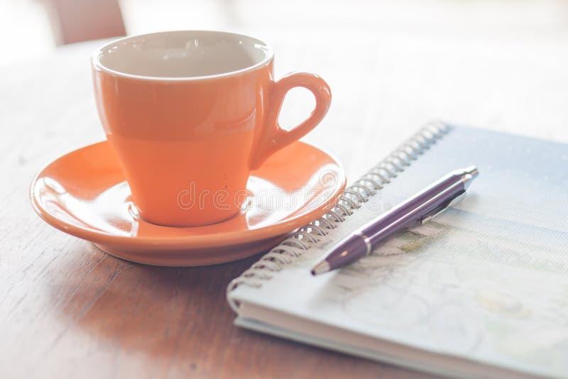 Filiżanka kawy z piórem i ślimakowatym notatnikiem zdjęcia stock