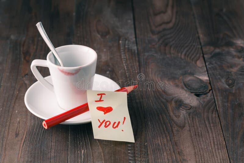 Filiżanka kawy z pomadki oceną, notatka i x27; kocham you& x27; na stole obrazy stock