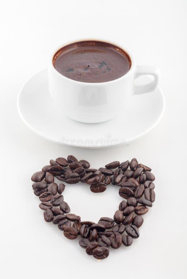 Filiżanka kawy z zawijas twarzą na wierzchołku z kształtem serce zdjęcia stock