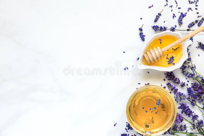 Filiżanka lawendowa herbata z miodowymi i świeżymi kwiatami nad bielu marmuru stołem Ziołowy napój Odgórny widok obrazy royalty free