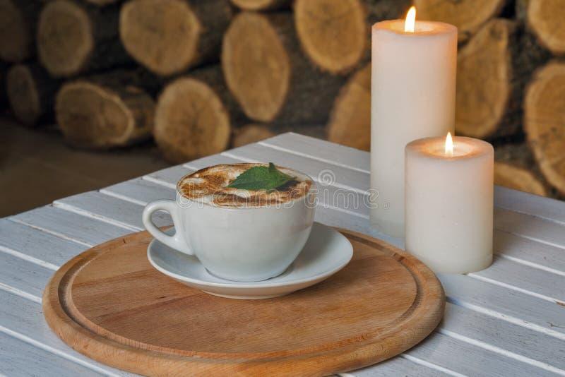 Filiżanka na bar stołowych i romantycznych świeczkach zbliżenie obraz stock