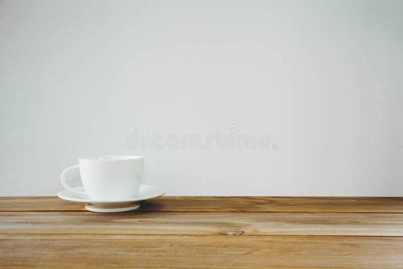 Filiżanka na drewnianym stole nad białym tłem Rocznika brzmienie zdjęcie stock