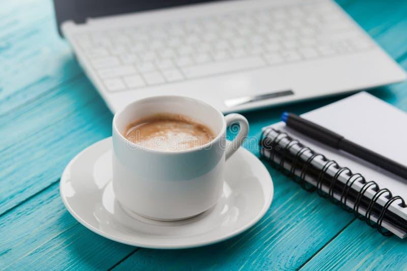 Filiżanka, notatnik i laptop na drewnianym turkusowym backgrou, obrazy stock