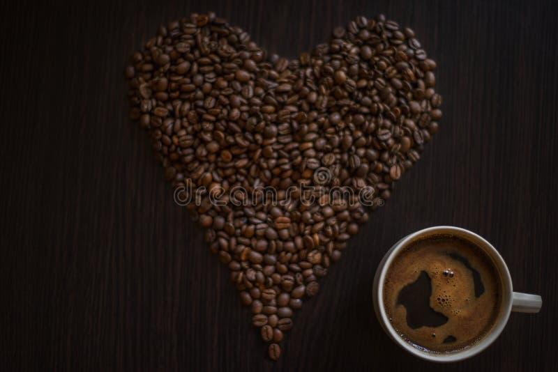 Filiżanka pełno kawa i piec kawowe fasole na drewnianym stole w postaci hearth obraz stock