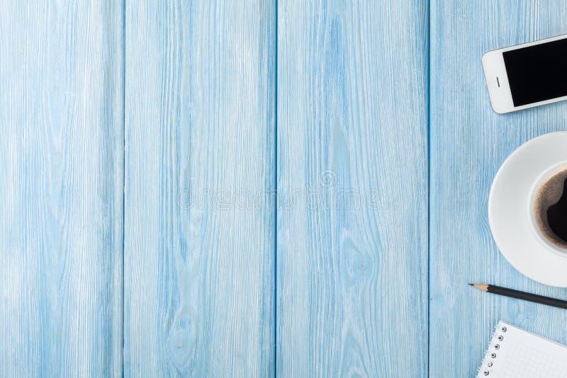 Filiżanka, smartphone i pustego miejsca notepad na drewnianym stołowym backgro, zdjęcie royalty free