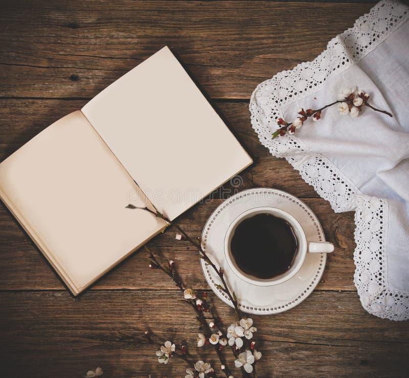 Filiżanka spodeczka kawowej białej książki drewniany tło fotografia stock