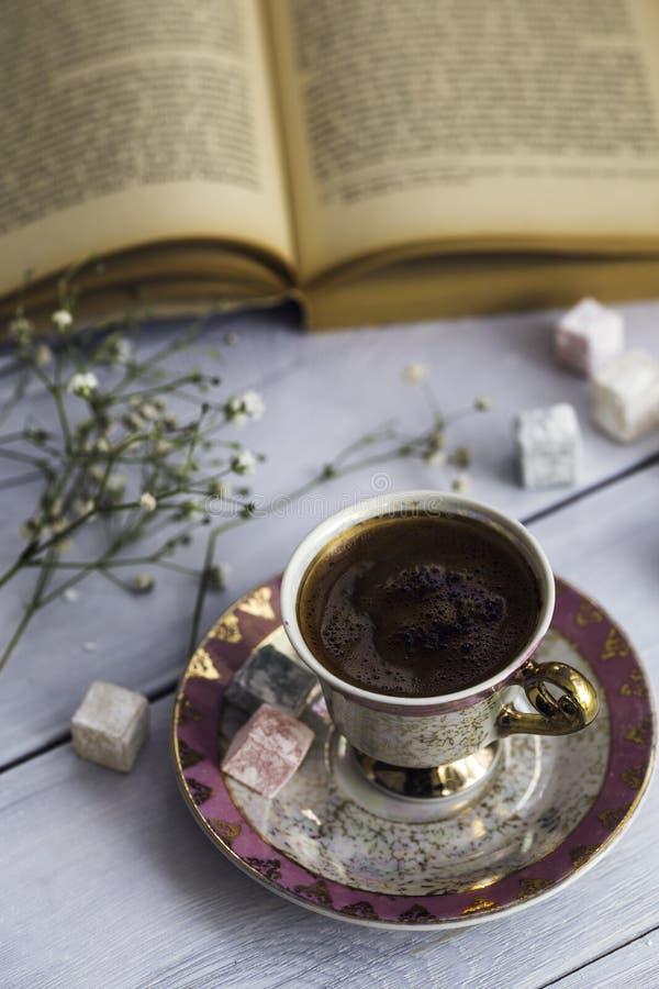 Filiżanka Turecka kawa z Tureckimi zachwytami i serce kształtował czekoladę obok starej książki obraz stock