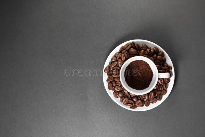 filiżanka z świeżo mleć piec kawowymi fasolami z owoc od kawowej rośliny z talerzem filiżanka z świeżo mlejący piec zdjęcie stock