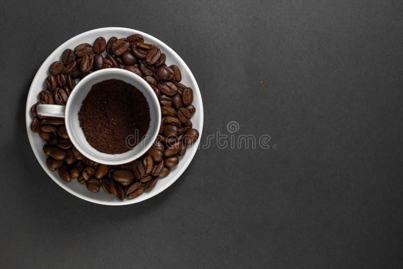 filiżanka z świeżo mleć piec kawowymi fasolami z owoc od kawowej rośliny z talerzem obrazy royalty free