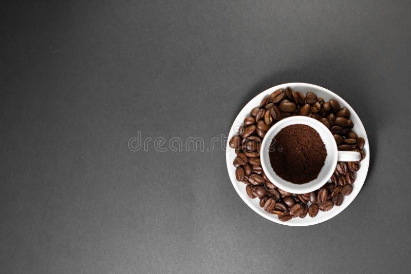 filiżanka z świeżo mleć piec kawowymi fasolami z owoc od kawowej rośliny z talerzem zdjęcia stock