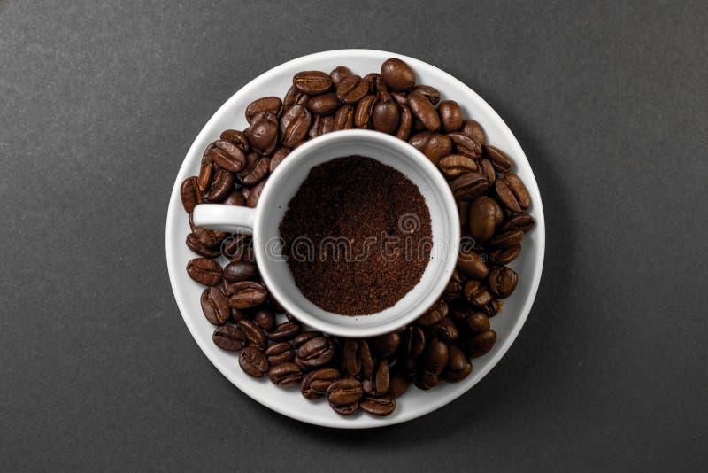 filiżanka z świeżo mleć piec kawowymi fasolami z owoc od kawowej rośliny z talerzem zdjęcia royalty free