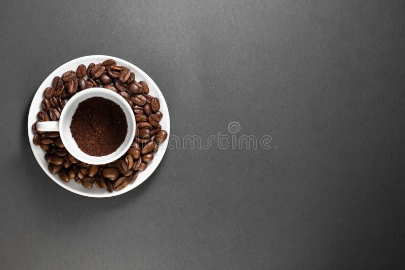 filiżanka z świeżo mleć piec kawowymi fasolami z owoc od kawowej rośliny z talerzem fotografia royalty free