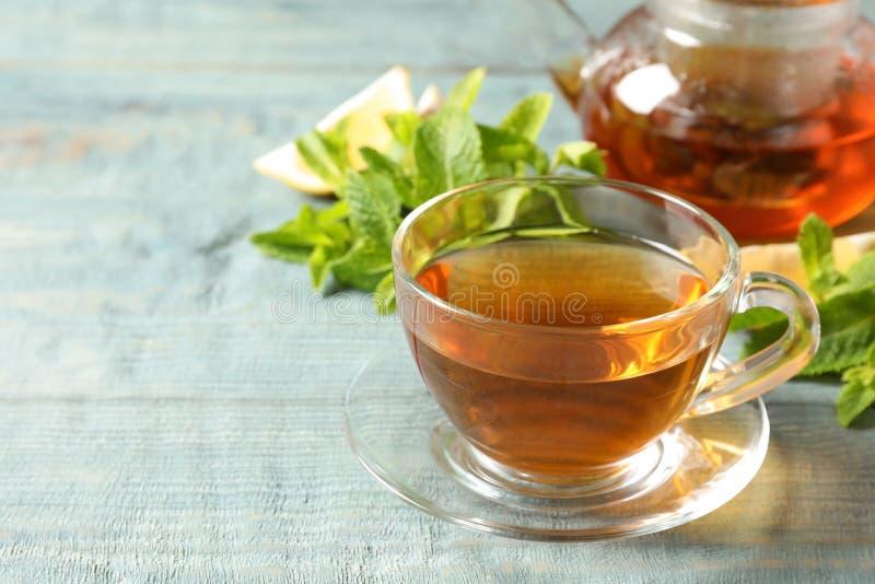 Filiżanka z aromatyczną nową herbatą i świeżymi liśćmi na stole zdjęcie stock