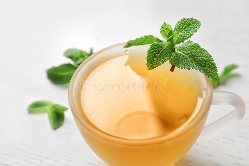 Filiżanka z gorącą aromatyczną nową herbatą i świeżymi liśćmi obraz royalty free