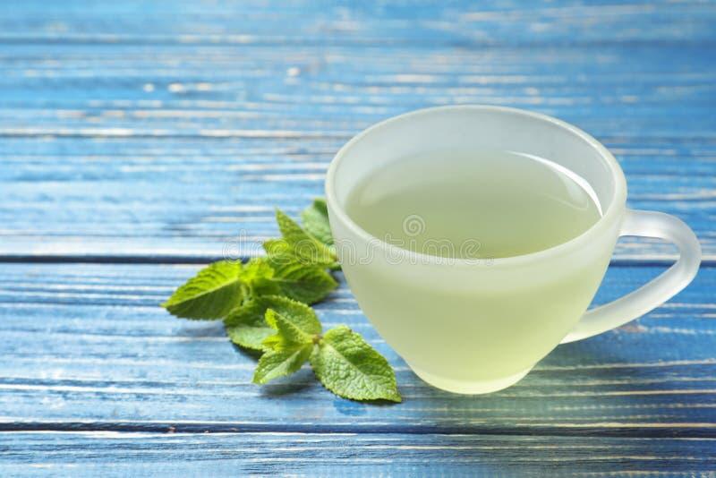 Filiżanka z gorącą aromatyczną nową herbatą i świeżymi liśćmi zdjęcia royalty free