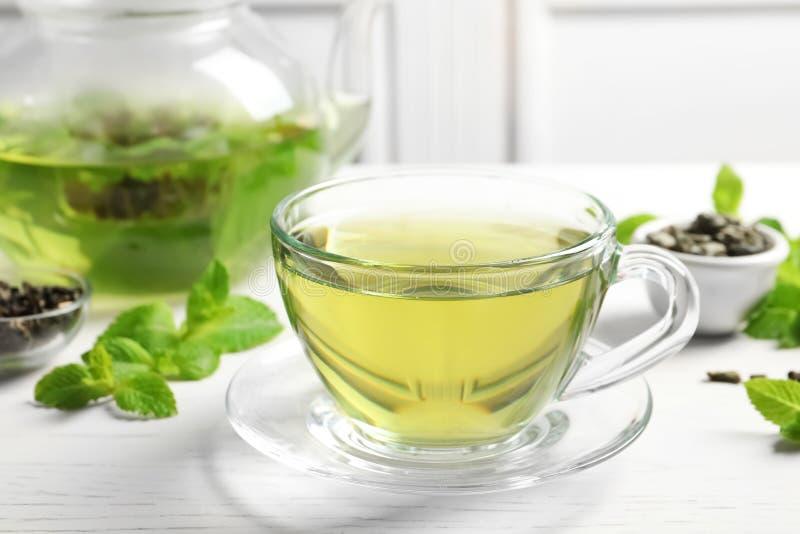 Filiżanka z gorącą aromatyczną nową herbatą i świeżymi liśćmi obrazy royalty free