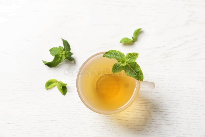 Filiżanka z gorącą aromatyczną nową herbatą i świeżymi liśćmi obraz stock