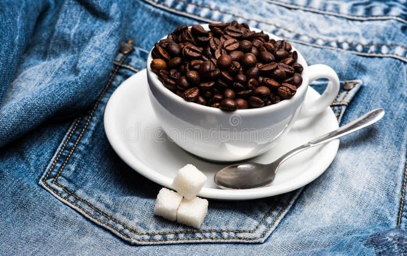 Filiżanka z kawowymi fasolami, dystyngowanym cukierem i łyżką na talerzu, drelichowy tło Świeży warzący kawowy pojęcie Kubek pełn zdjęcie royalty free
