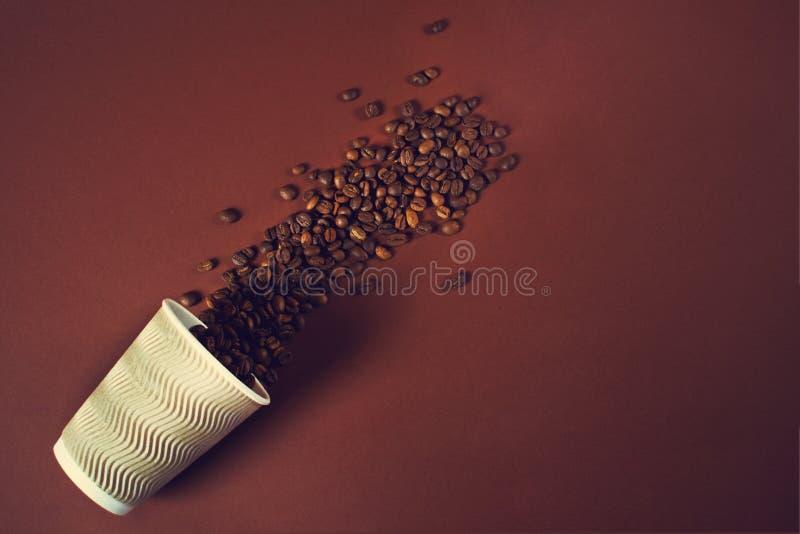 Filiżanka z kawowymi fasolami spadać za stole dalej obraz stock