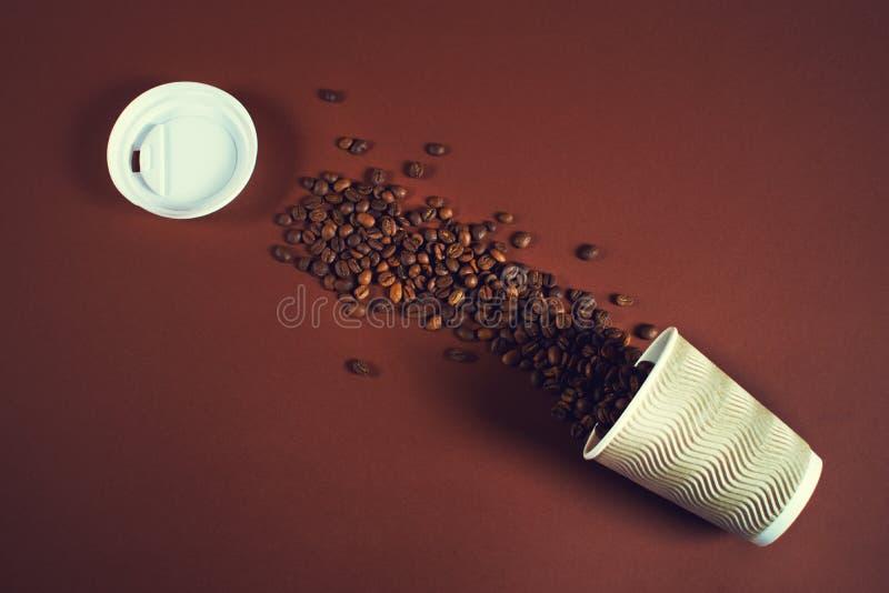 Filiżanka z kawowymi fasolami spadać za stole dalej zdjęcie royalty free