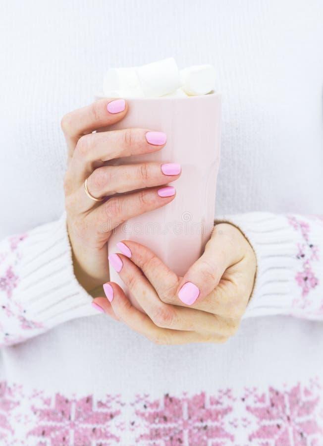 Filiżanka z marshmallows w żeńskich rękach zdjęcia royalty free