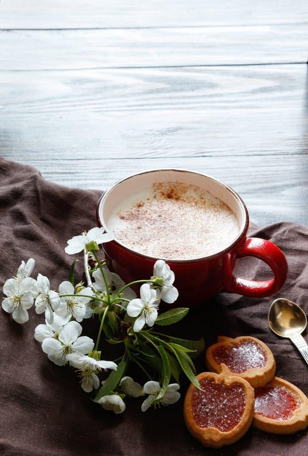 Filiżanka z okwitnięciem i ciastkami kawowym i czereśniowym zdjęcia royalty free