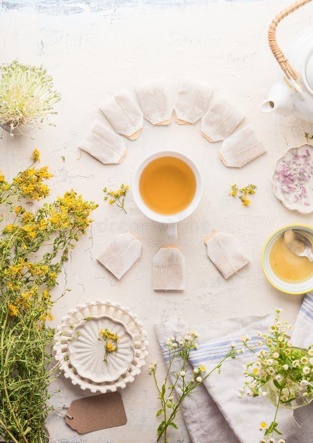 Filiżanka z ramą herbaciane torby ziołowa herbata na bielu stołu tle, odgórny widok Ziołowej herbaty położenie z teapot, miodowy  zdjęcia royalty free