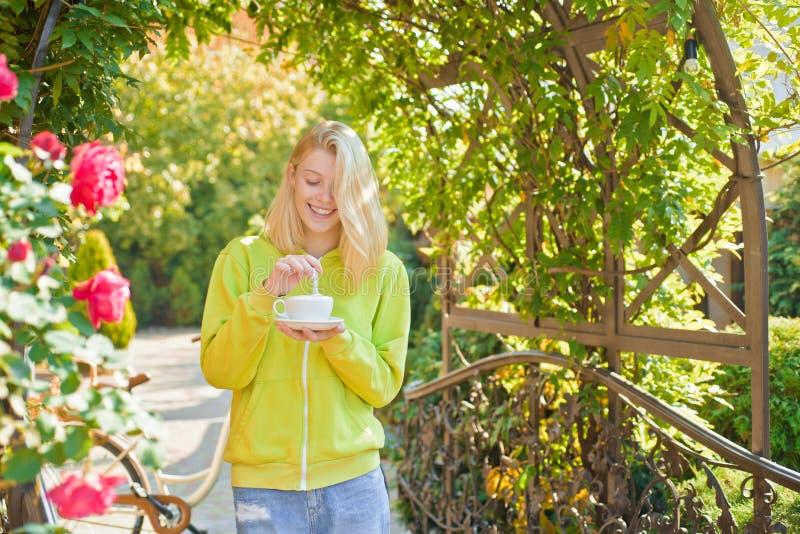 Filiżanka zachwyt Hedonizm i smakosz Cieszy się wyśmienicie śmietankowego cappuccino w kwitnienie ogródzie Dziewczyna napoju smak zdjęcie royalty free