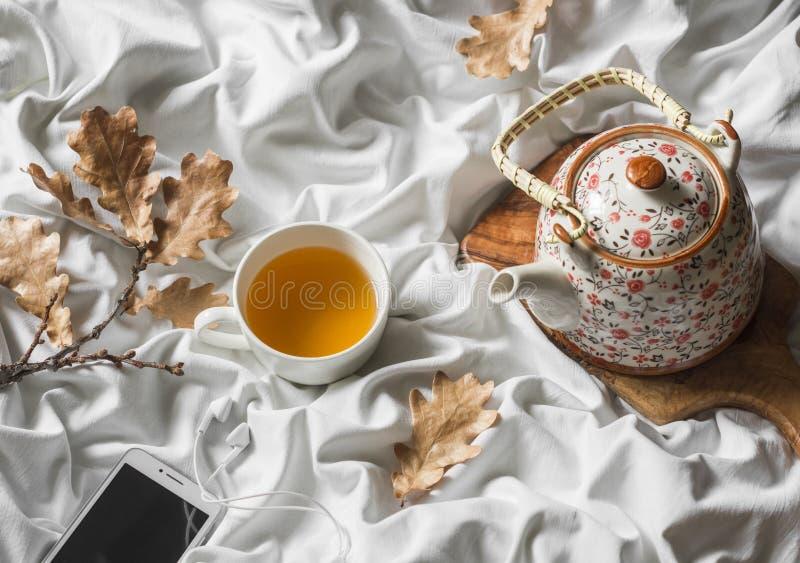 Filiżanka zielona herbata, hełmofony, gracz, teapot w łóżku, odgórny widok Gnuśny ranek, ciepły jesień nastrój obrazy royalty free