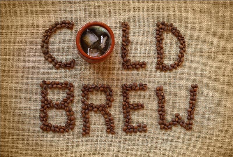 Filiżanka zimno warzył kawę z kawowymi fasolami zdjęcia royalty free
