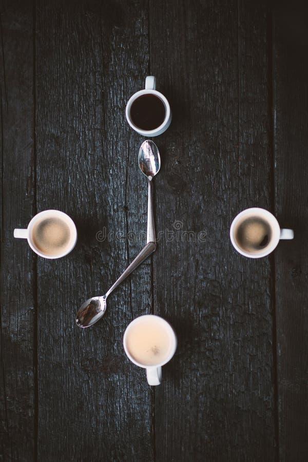 Filiżanki aranged jako zegarowa twarz na drewnianym czarnym tle Cztery kawa espresso kubka jak symbol czas z dwa łyżkami Czas f zdjęcie royalty free