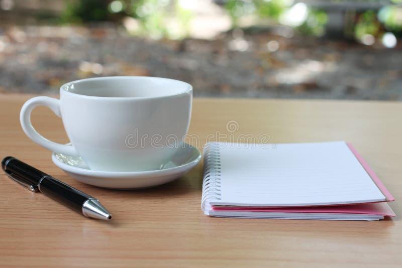 Filiżanki i notatnika pióro umieszcza na brązu drewnianym stole a fotografia stock