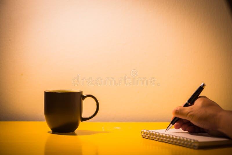 filiżanki i ręki writing na stole z lampą przy nighttime, v fotografia royalty free