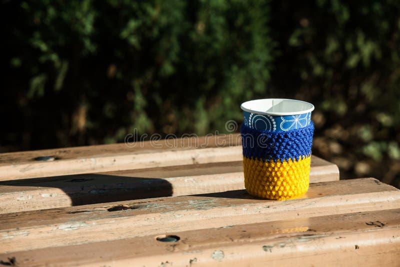 Filiżanki kawowa drewniana ławka zakrywał śnieżnego mornimg upału żółtego błękitnego dzianie fotografia stock