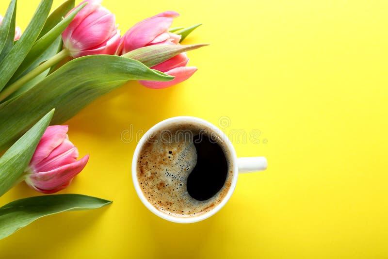 Filiżanki kawy i menchii tulipany na żółtym tle, odgórny widok zdjęcia stock